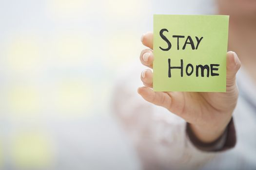Hand holding sticky note with Stay Home text