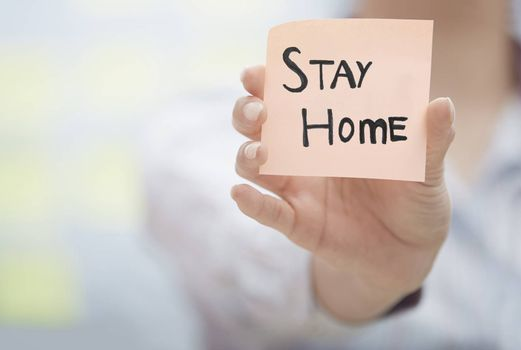 Hands holding sticky note with Stay Home text