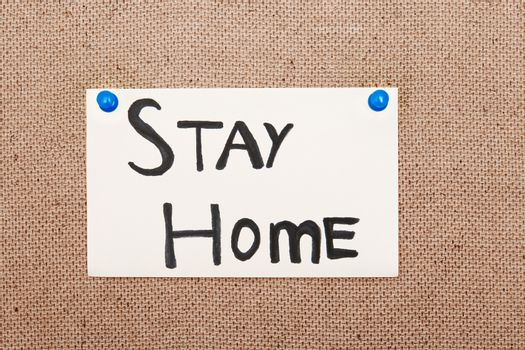 Adhesive note with Stay Home text attached to the bulletin board by pushpins
