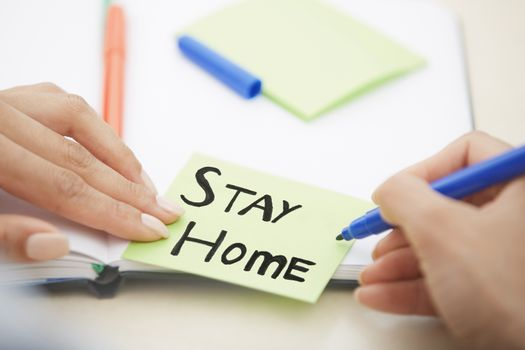 Hands of woman writing on adhesive note with Stay Home text