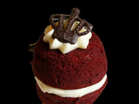 Closeup of a red velvet cake topped with a chocolate crown isolated on black background