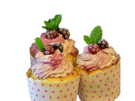 Closeup of tasty muffins with cream and berries in a paper packaging