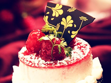 Soft focus of a cake topped with re berries and chocolate