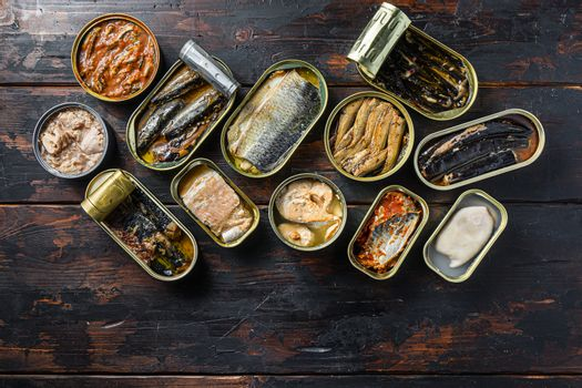 opened cans conserve with Saury, mackerel, sprats, sardines, pilchard, squid, tuna over wood table top view