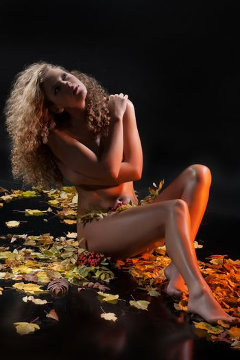 Young nude woman and yellow autumn leaves on a studio background