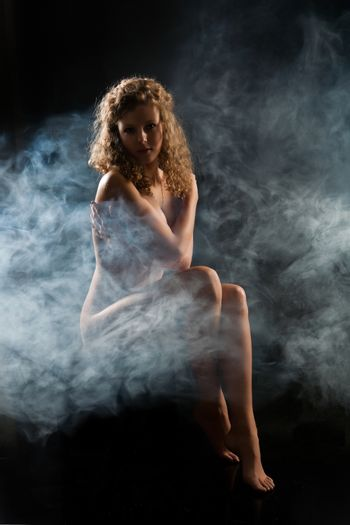 Young nude woman in a smoke ona studio background