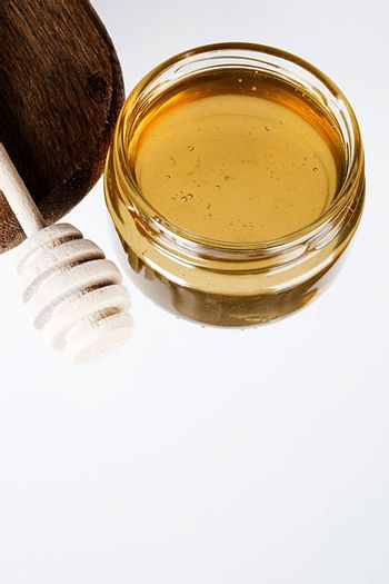 Glass bowl with honey and a wooden dipper on white background