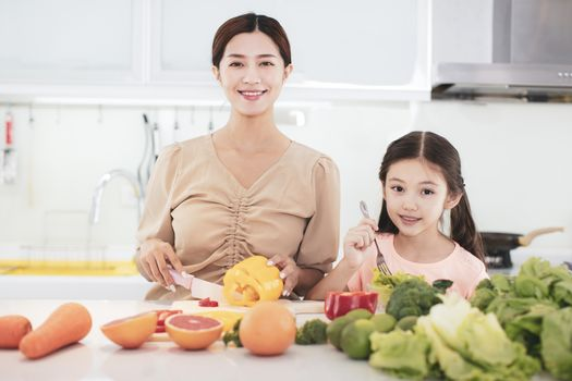 happy Mother and child daughter  preparing the vegetables and fruit