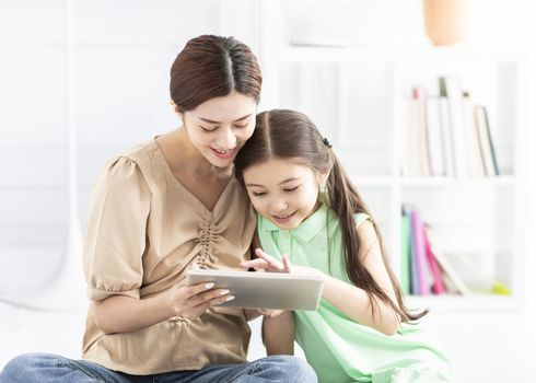 mother and daughter doing homework with  tablet