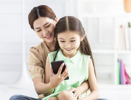 happy mother and daughter watching the smart phone