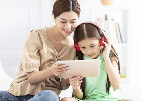 mother and daughter learning  with  tablet at home