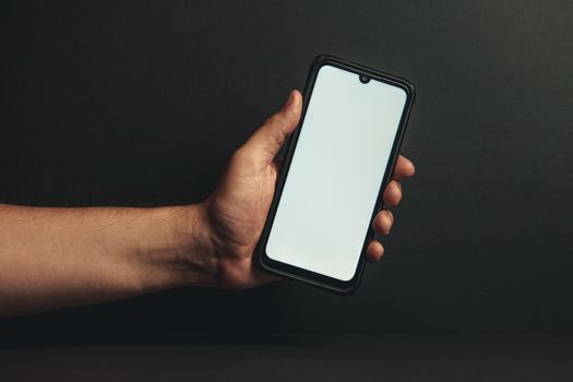 Hand holding a phone with a white screen