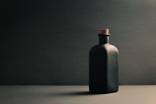 Single black ceramic bottle over a dark background