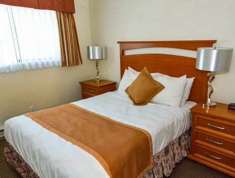 Double bed in the bedroom with the lamp on bedside tables