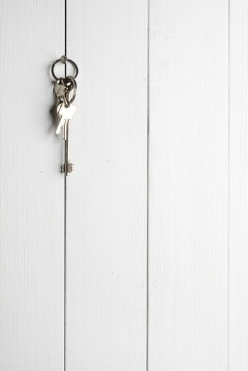 a bunch of keys hanging on a white wooden wall
