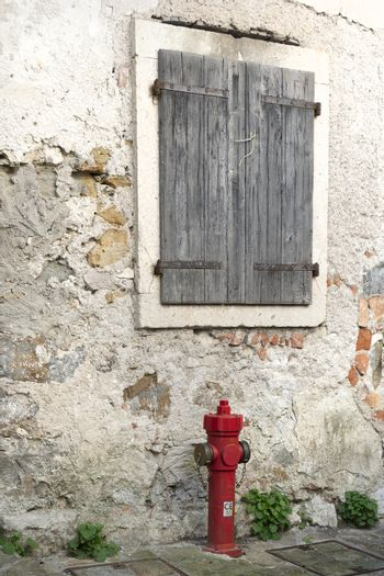 a red fire hydrant at the edge of a old street