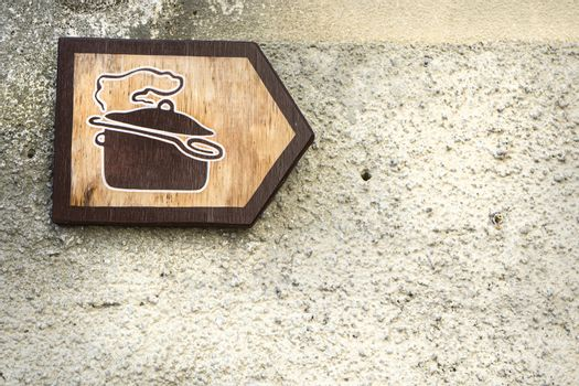 a wooden sign indicating a restaurant on the right