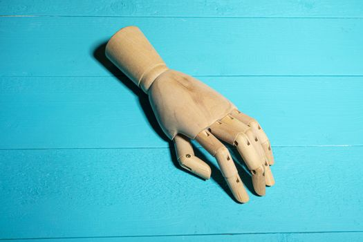 A wooden hand on a blue table