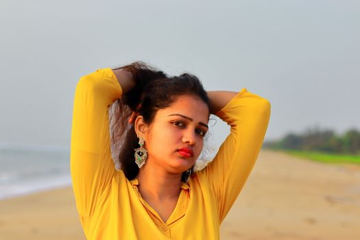 A asian beautiful girl standing on the beach and holding her hairs with yellow top, head shot