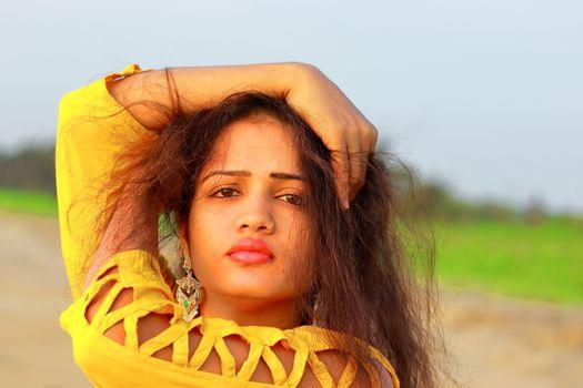 closeup of A fashionable Indian model girl in yellow top, head shot