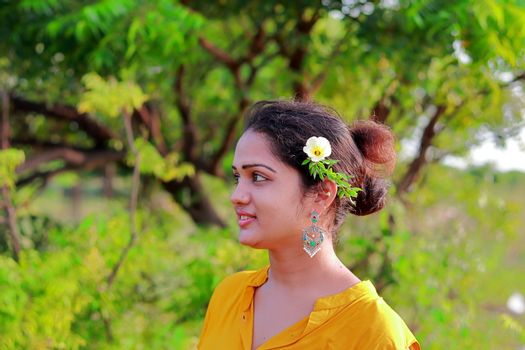 Photo of an Indian young girl with flower in creative hairs