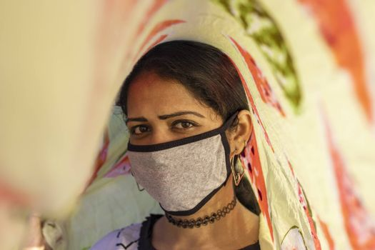 An Indian young girl creative photo taken with a scarf and wearing face mask Protection against disease, coronavirus.
