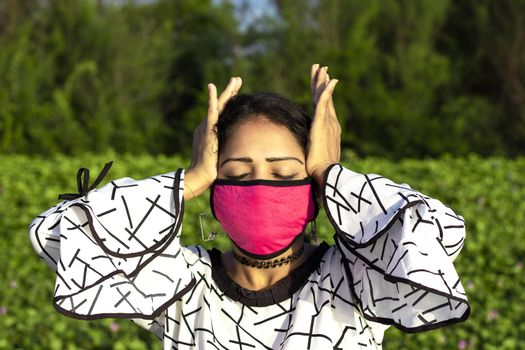stylish Woman wearing protective pink face mask and posing on natural green background. Stressed Exhausted Young lady Having Strong Tension Headache.