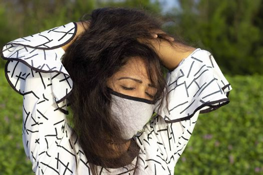 stylish Woman wearing protective face mask and posing on outdoors natural green background.