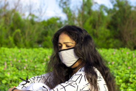 Portrait of a stylish young girl sitting in the nature and wearing face mask Protection against disease, coronavirus.