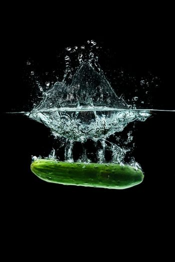 Cucumber splashing water isolated onblack background. Healthy food concept
