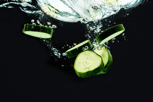 Sliced bio cucumber splashing water isolated on black background. Skin moisturizing cosmetics concept