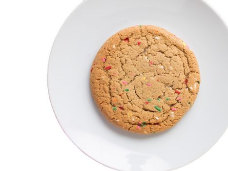 Almond giant biscuits with coloured sugar pieces on a white platter