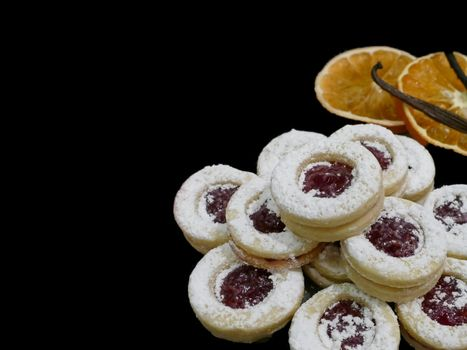 Strawberry Christmas biscuits and orange slices with cinnamon sticks on a black background
