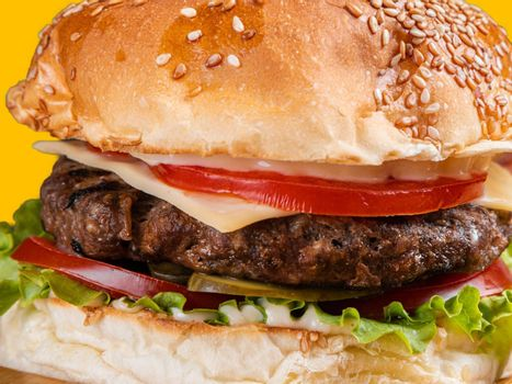 A close up of a delicious hamburger with beef, cheese, and vegetables