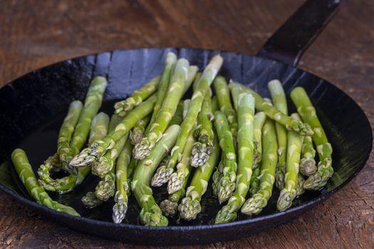 fresh green asparagus in a pan on dark wood