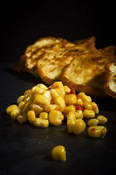 Corn and corn pancakes on black background
