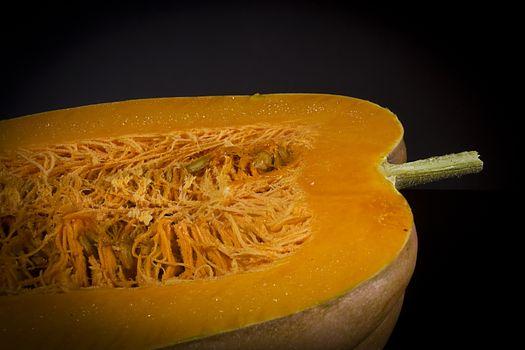 Cut ripe orange pumpkin on black background
