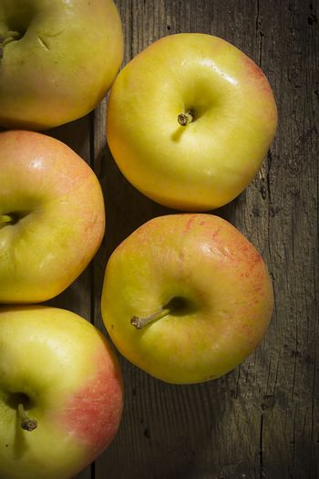 Lots of ripe apples on an old wooden surface