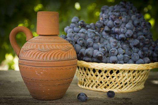 Clay jug with wine and grapes outdoors