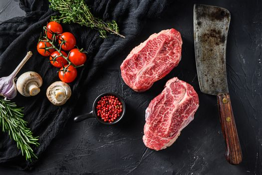 Raw top blade cut organic meat ner butcher meat clever knife for bbq or grill top view over black stone background