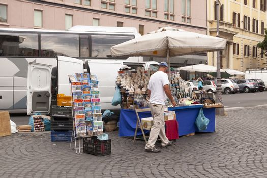 Rome, Italy - June 27, 2010: A man sells souvenirs to the tourists at his street stall, in Rome.