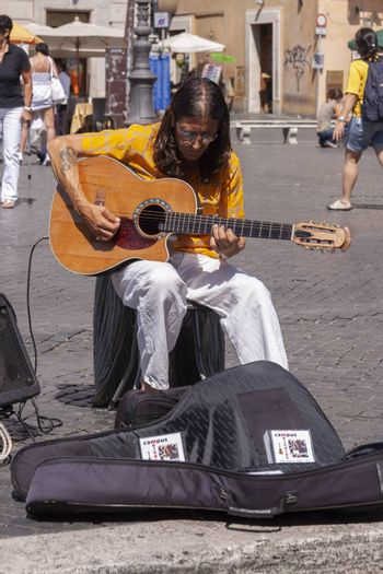 Rome, Italy - June 28, 2010: A busker man, works and begs for alms, playing the guitar in Piazza Navona, Rome.