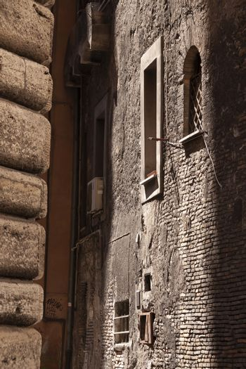 Rome, Italy - June 28, 2010: Old houses and walls in an alleyway between two streets in the center of Rome.