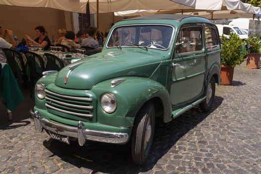Rome, Italy - June 28, 2010: An old vintage car, Fiat brand, a classic from the 60s, remains parked in one of the central streets of Rome