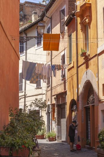 Rome, Italy - June 28, 2010: A man scrubs and cleans the portal of a house, in one of the central streets of Rome, while the hanging clothes are dried in the air.