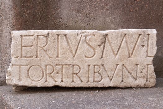 Rome, Italy - June 28, 2010: Ancient Latin inscription, carved from a heavy block of white marble, from the time of the Roman Empire.