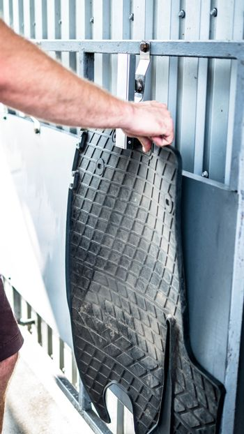 A man holds a dirty car rug in his hand,car wash,close-up.A man working at a car wash.