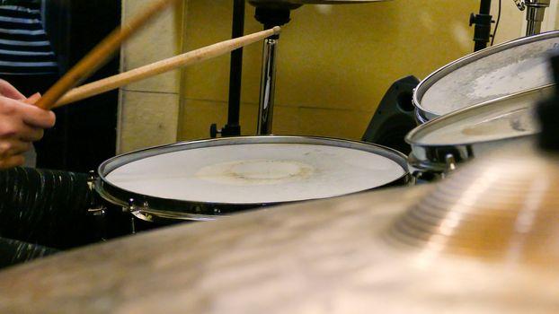 Sticks playing drums on drumkit