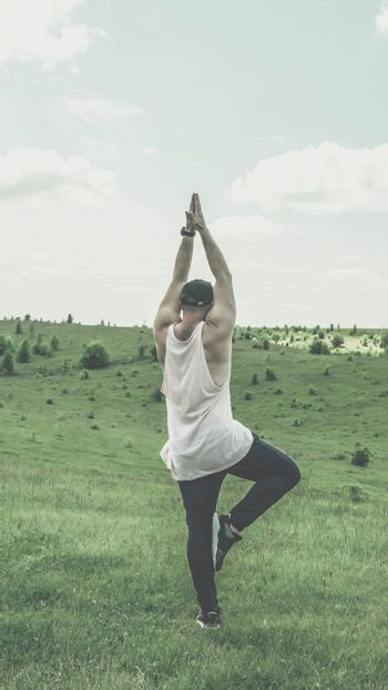A young guy does exercises in nature,a man does exercises in a field in a meadow,a dreamy man, a lonely man