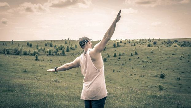 A dreamy guy in a field with outstretched arms,a free man,a young guy demonstrates freedom,a man pretends to fly